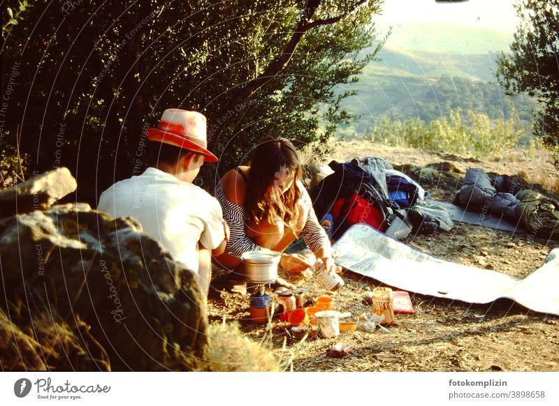 junge Frau und junger Mann beim Camping Kochen in warmer südländischer Landschaft Paar roadtrip Campingplatz Essen zubereiten Sommer Abenteuer Mann und Frau