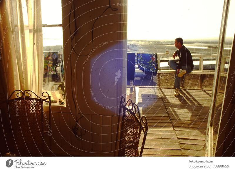 junger Mann sitzt auf einer Terasse und blickt in die Ferne Strandurlaub Fensteraussicht sitzen warten Balkon Strang Ferien pausieren Sommer Urlaub freizeit