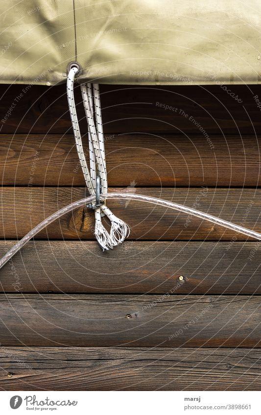 Befestigung mit doppeltem Nutzen. Seil hält die Plane und auch eine Kunststoff-Leuchtschnur Holz Bretterwand Sicherung sichern Schutz Schützen parallel