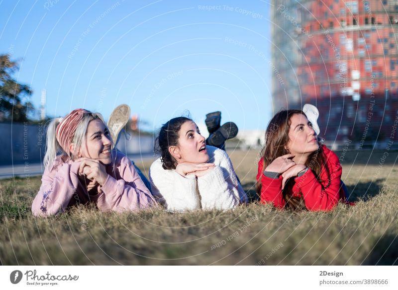 Drei schöne junge Frauen liegen auf dem Rasen, ruhen sich aus und träumen im Park auf dem grünen Gras. Glück Lügen drei Lächeln Freundschaft Boden Freunde