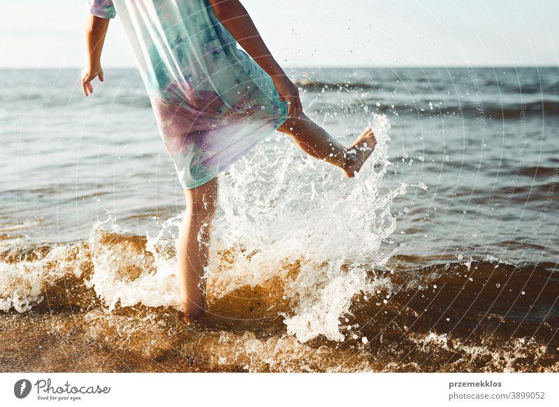 Mädchen, das seine Freizeit damit verbringt, in den Sommerferien am Strand ins Meer zu springen aufgeregt frei genießen positiv Sonnenuntergang Emotion