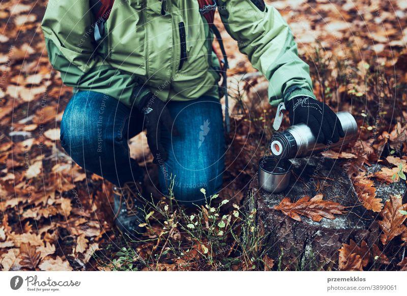 Frau mit Rucksack macht während einer Herbstreise am kalten Herbsttag Pause und gießt ein heißes Getränk aus der Thermoskanne im Freien Ausflugsziel wandern