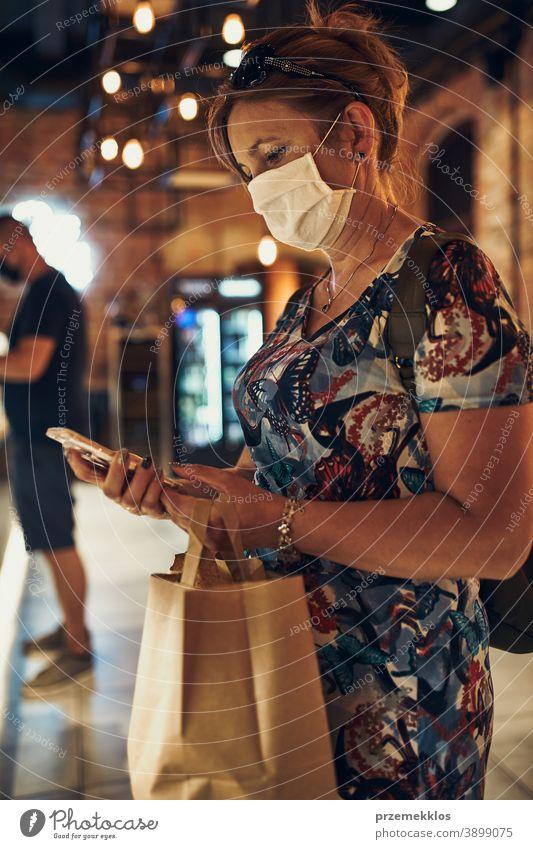 Junge Frau beim Einkaufen im Lebensmittelgeschäft, die die Gesichtsmaske trägt, um eine Virusinfektion zu vermeiden Kaukasier Gespräch covid-19 Lifestyle