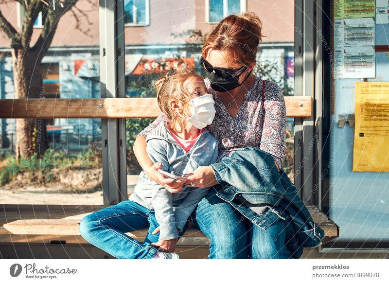 Frau und ihr Kind warten an einer Haltestelle des öffentlichen Verkehrs auf einen Bus Bushaltestelle Warten Mundschutz Gesicht Pandemie Coronavirus Ausbruch