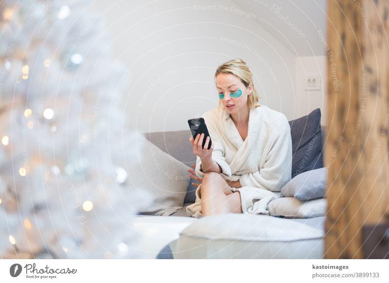 Junge Geschäftsfrau im kuschelig warmen Bademantel und mit kosmetischen Augenklappen, die während der Coronavirus-Pandemie 2020 in der winterlichen Weihnachtszeit fernab von zu Hause arbeitet. Arbeit von zu Hause aus, Selter an Ort und Stelle, Konzept.