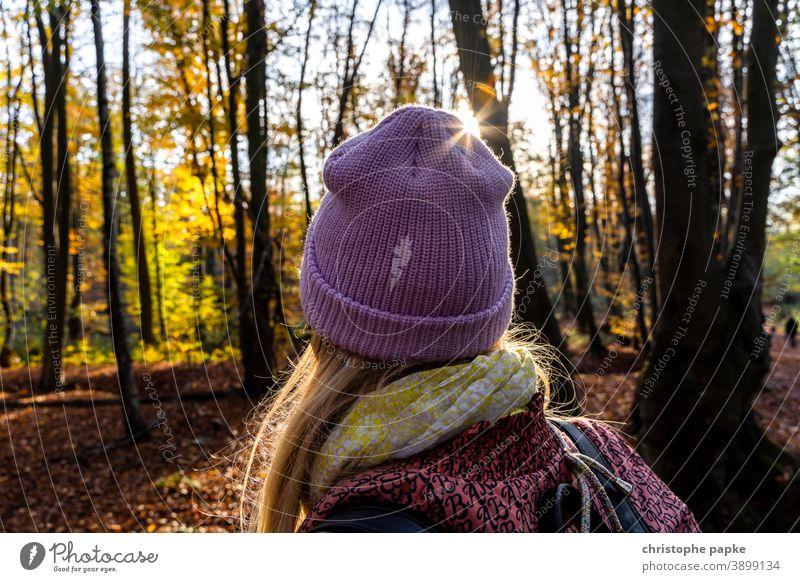 Frau mit Mütze beim Spaziergang im herbstlichen Wald Herbst Gegenlicht Sonnenlicht kalt Außenaufnahme Rückansicht Mensch Baum Erwachsene Landschaft Farbfoto Tag