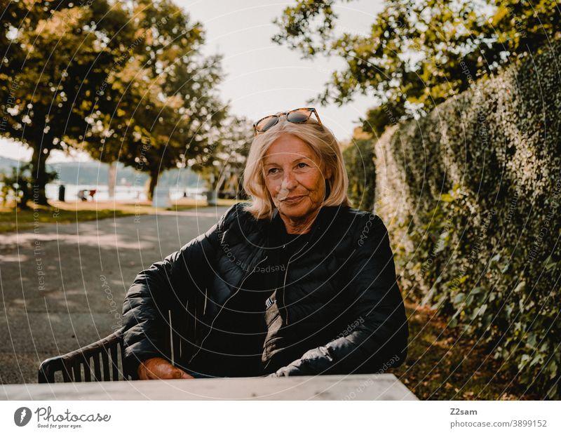 Modische Rentnerin sitzt am Ufer des Attersees attersee seeufer Café Berge u. Gebirge Landschaft Natur Farbfoto Umwelt Schönes Wetter sonne sommer entspannung