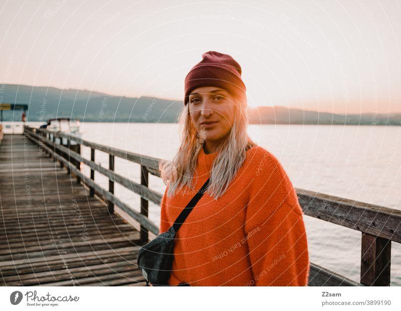 Junge Frau in der Abendsonne am Attersee attersee abendrot sonnenuntergang Natur Abenddämmerung Landschaft idylle österreich steg seeufer Außenaufnahme orange