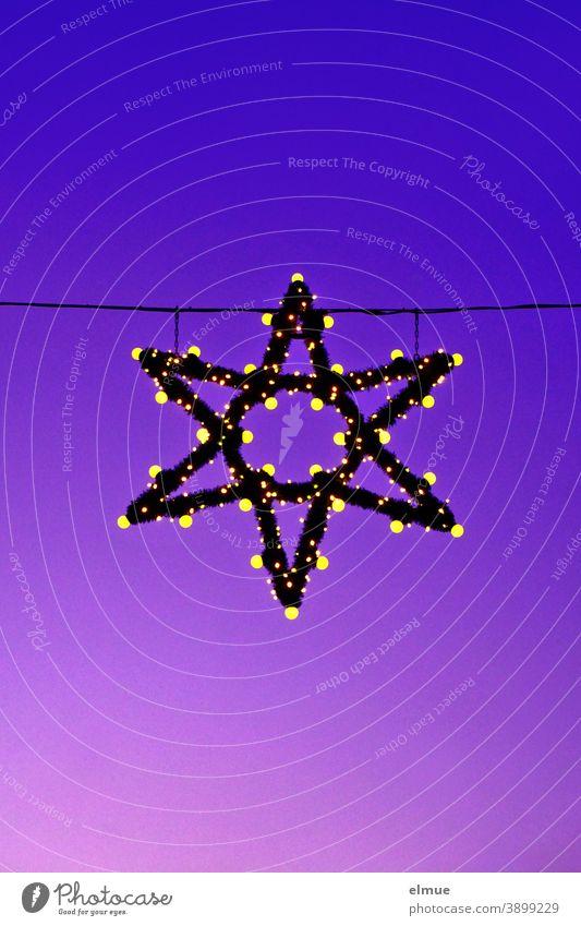 ein grüner Weihnachtsstern leuchtet in der anbrechenden Nacht / Weihnachtsdekoration / Advent Stern leuchten Lampen Glühlampen Leuchtmittel lila blau hängen