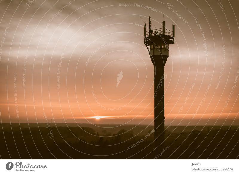 Sonnenuntergang am nebeligen Horizont mit einem Feuerwachturm im Vordergrund Nebel rot orange Feuerwache Feuerwehr Waldbrand waldbrandgefahr Brand Brandwache