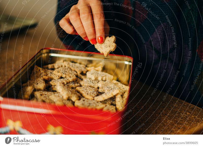 Frau nascht Weihnachtsplätzchen aus einer Plätzchendose naschen Weihnachten Weihnachtsnascherei Weihnachten & Advent Backwaren süß Keksdose Hand weiblich Mensch