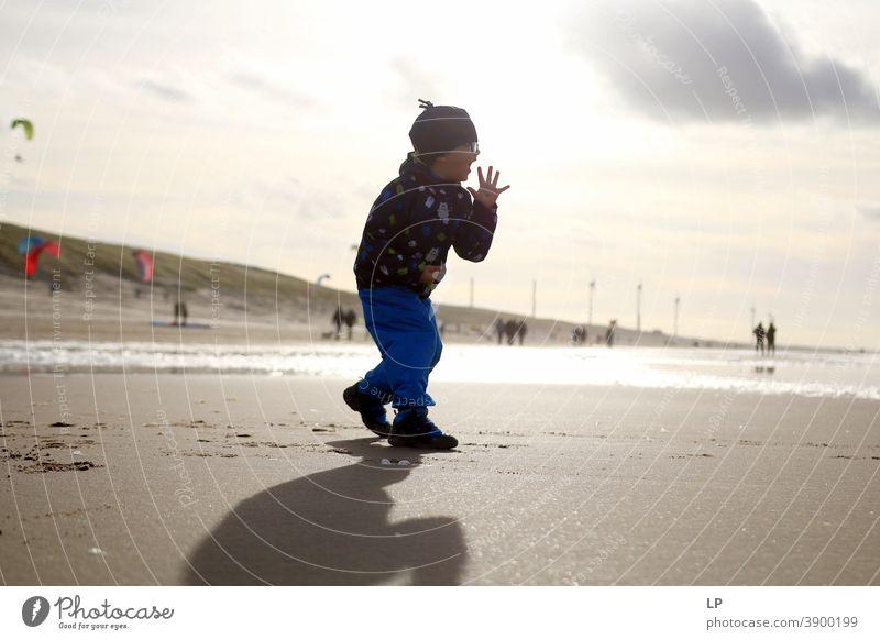 Silhouette eines Jungen am Strand, der glücklich ist Glaube und Religion betend Gebet Hintergrund weitergeben Zufriedenheit Körperhaltung
