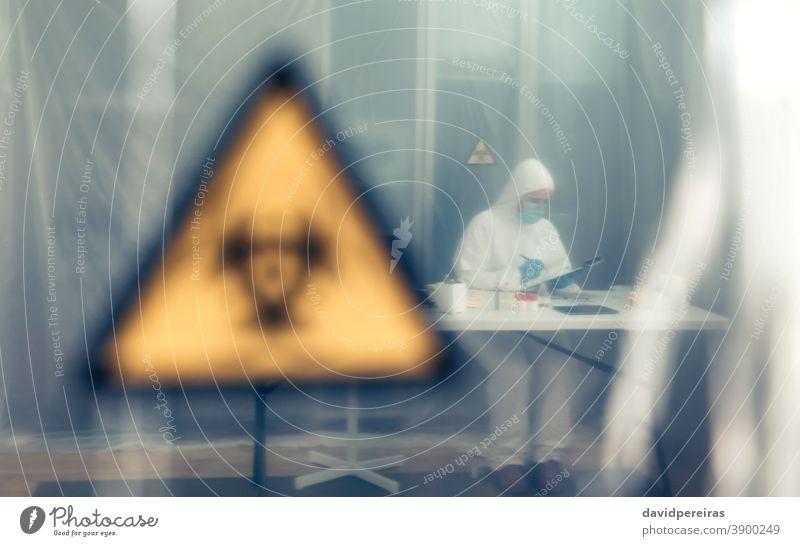 Wissenschaftlerin untersucht im Labor hinter einem Schutzvorhang Isolation Coronavirus Symbol für Biogefährdung bakteriologischer Schutzanzug Erkundung Virus
