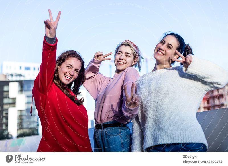 Frontansicht von drei Teenager-Mädchen, die an einem sonnigen Tag im Freien ein Friedenszeichen machen Sieg Zeichen Kaukasier heiter niedlich Ausdruck