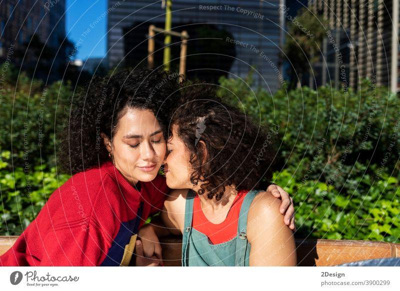 Lächelndes lesbisches Paar, das sich auf einer Parkbank umarmt und entspannt anhänglich Nähe umarmend ethnisch Ethnizität Freunde Freundschaft Lachen Liebhaber