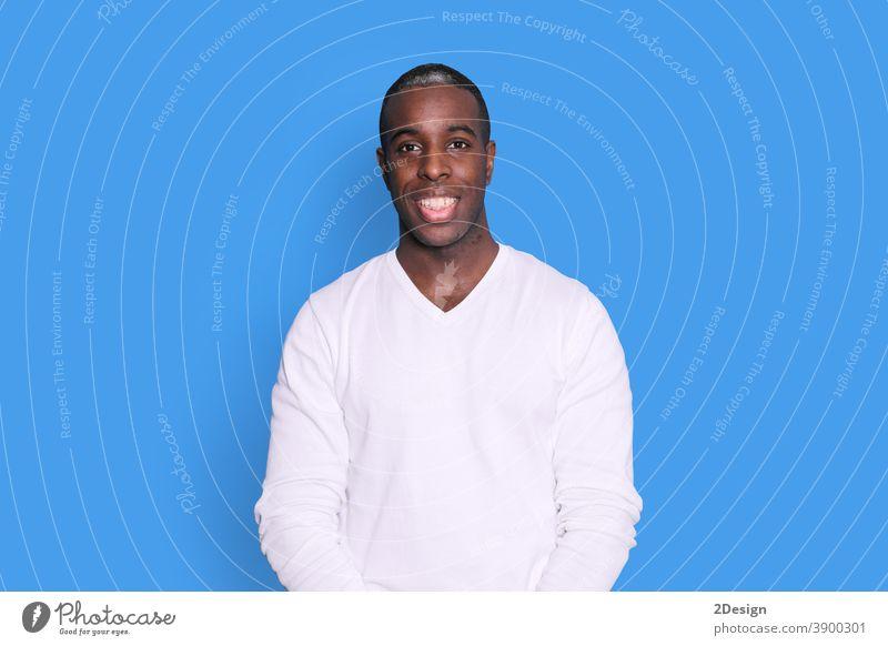 Lächelnder junger afroamerikanischer Mann in lässigem weißem Pullover, der isoliert auf pastellblauem Hintergrund auf einem Studioporträt posiert. Menschen aufrichtige Emotionen Lifestyle-Konzept. Mock up Kopierraum. Blick in die Kamera.