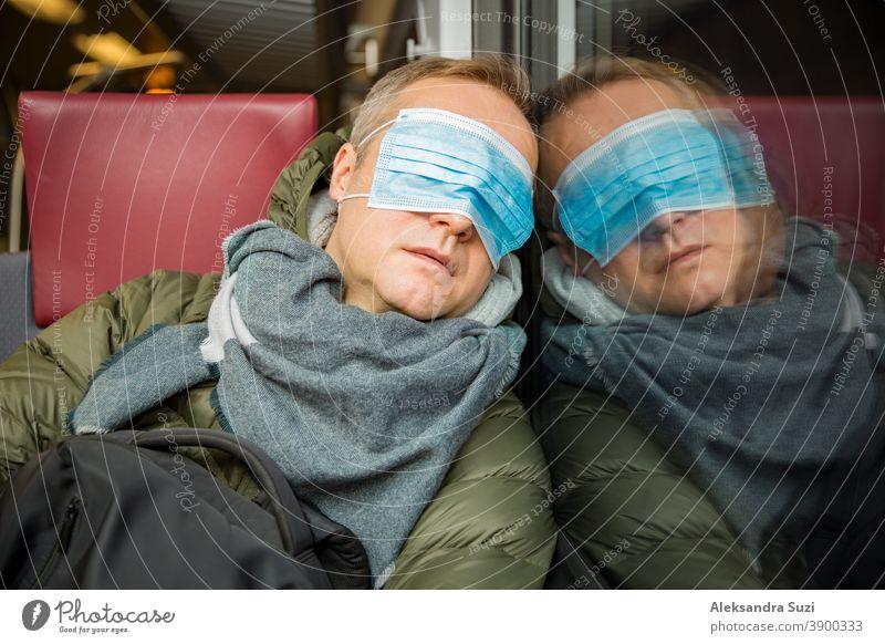 Reisen in öffentlichen Verkehrsmitteln während der Pandemie. Ein müder Mann mittleren Alters mit einer medizinischen Schutzmaske auf dem Gesicht schläft im Nahverkehrszug.