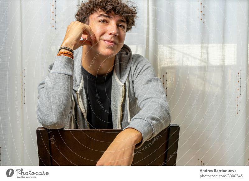 Attraktiver junger Mann mit lockigem Haar trägt ein graues Sweatshirt und posiert auf weißem Vorhanghintergrund heiter lässig Hemd Lächeln Behaarung männlich