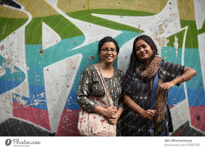 Porträt von zwei indisch-bengalischen brünetten Frauen/Freunden/Schwestern vor einer Graffiti-Wand. Indischer Lebensstil Schauspielerin Erwachsener asiatisch