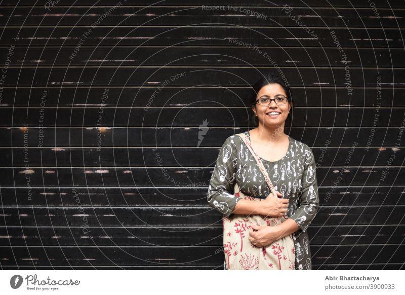 Porträt einer indisch-bengalischen brünetten Frau vor einer Wand/Metallic-Tor/ schwarz strukturierter Hintergrund. Indischer Lebensstil Schauspielerin