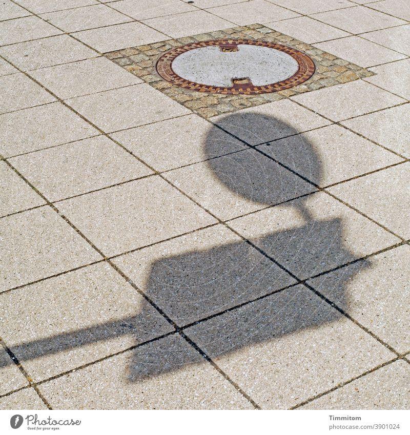 Hallo Du da!? Gullydeckel Schatten Verkehrsschild Platten Platz Linien und Formen Annäherung Nähe Strukturen & Formen Menschenleer