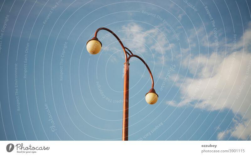Straßenlampe Peitschenlaterne Lampe Straßenbeleuchtung Licht Himmel blau Laternenpfahl Wolken Tag Stadt Metall Großstadt Straßenlaterne Farbfoto leuchten
