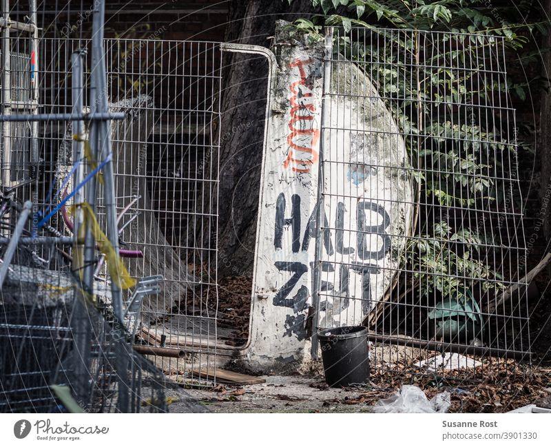 Ein kaputter Bauzaun, davor und dahinter Bauschutt, mit Graffiti bemalt. Mit schwarzer Farbe ist das Wort Halbzeit auf ein halbrundes Bauelement geschrieben.