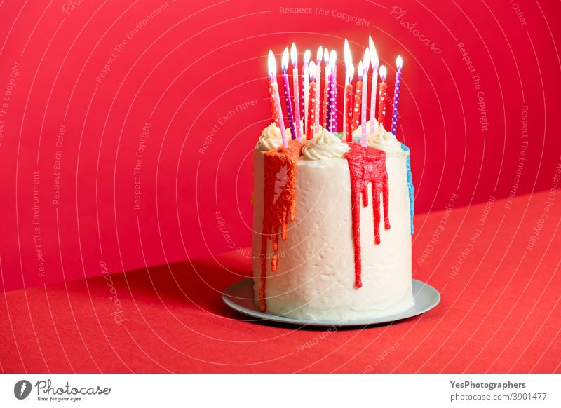 Geburtstagskuchen mit Kerzen auf rotem Hintergrund. Festliche Buttercremetorte Jahrestag Geburtstagstorte Kuchen Kerzenschein zu feiern Feier farbenfroh