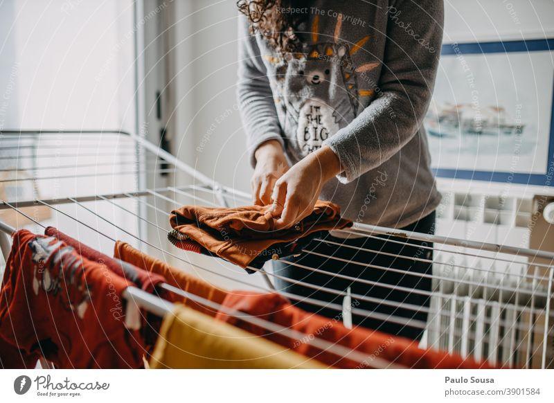Frau trocknet Wäsche innen Wäscheleine Kleidung Wäscheständer im Innenbereich heimisch häusliches Leben Haus Haushalt Haushaltsführung Mutter Mutterschaft