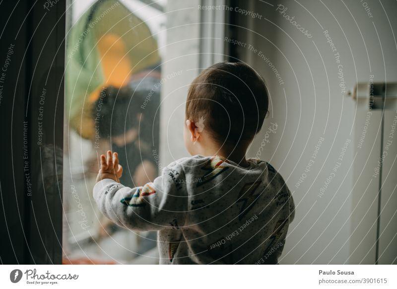 Kind beobachtet Mutter durch das Fenster Kindheit Kleinkind Kaukasier Rückansicht Tag Familie & Verwandtschaft Mensch 1-3 Jahre Farbfoto Lifestyle zu Hause