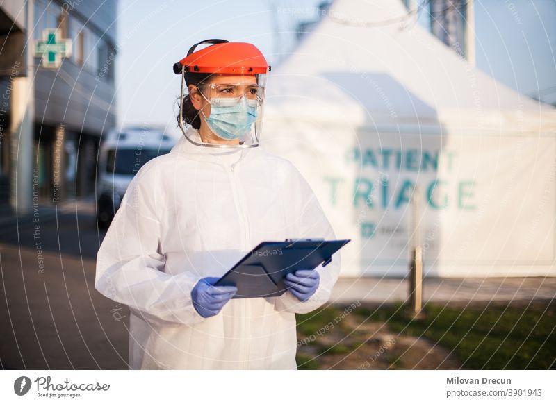 Sanitäter mit persönlicher Schutzausrüstung PSA mit Mappe vor der Isolierung des ICU-Krankenhauses stehend rt-PCR-Fahrt durch das Testgelände,COVID-19-Pandemieausbruchskrise,besorgt erschöpftes Personal