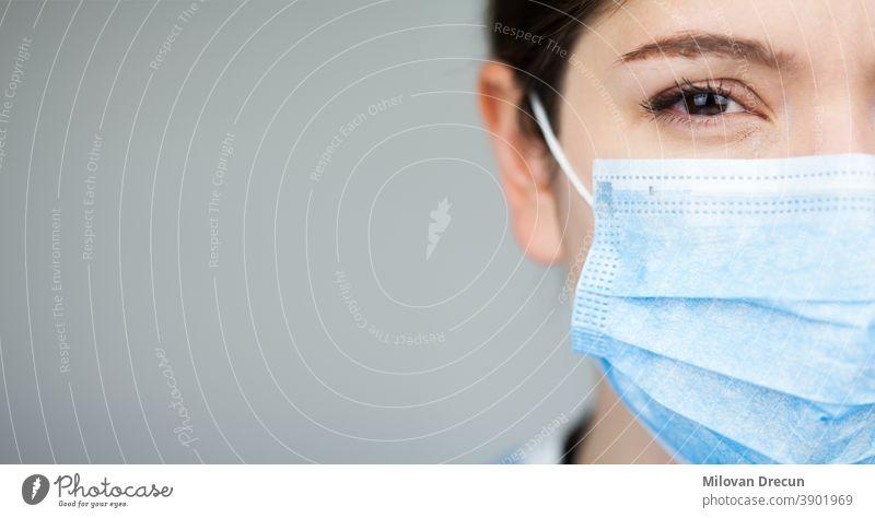Nahaufnahme des Gesichts einer Ärztin des britischen NHS EMS, die eine blaue PSA-Schutzmaske trägt,COVID-19 Coronavirus-Krankheit,globaler Ausbruch einer Pandemie,tödliche SARS-CoV-2-Epidemie,Kopierfeld auf der linken Seite des Rahmens