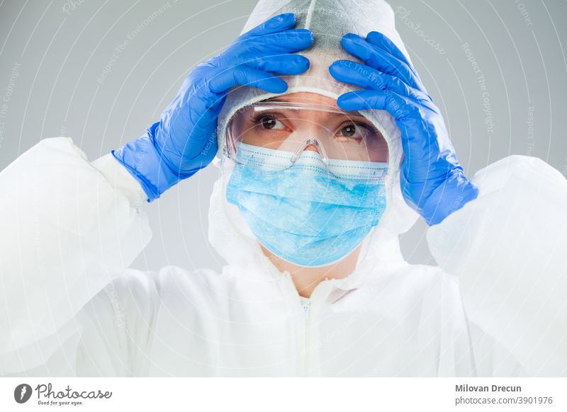 Verzweifelter medizinischer NHS-EMS-Mitarbeiter in weißem Schutzanzug, blauer OP-Maske, Latex-Handschuhe und Schutzbrille, Coronavirus-COVID-19-Pandemie-Krise, die einen Mangel an persönlicher Schutzausrüstung verursacht