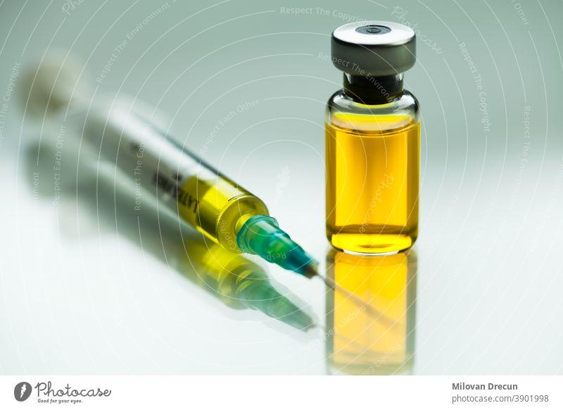 Spritze mit Nadel & Ampulle mit gelber Flüssigkeit,Illustration eines potentiellen Impfstoffs gegen das Coronavirus,bahnbrechende Heilung & Therapie der COVID-19 Viruskrankheit,SARS-CoV-2 Heilmittel & Immunisierung,W.H.O.