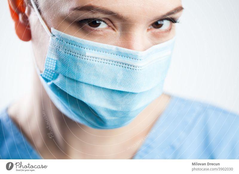 Junge Frau Nahaufnahme Detail Kopf, trägt blaue Kittel und schützende Gesichtsmaske, attraktive schöne kaukasische Ärztin, die in die Kamera starrt, hübsche Augen, die einen aussagekräftigen Blick geben, Coronavirus COVID-19