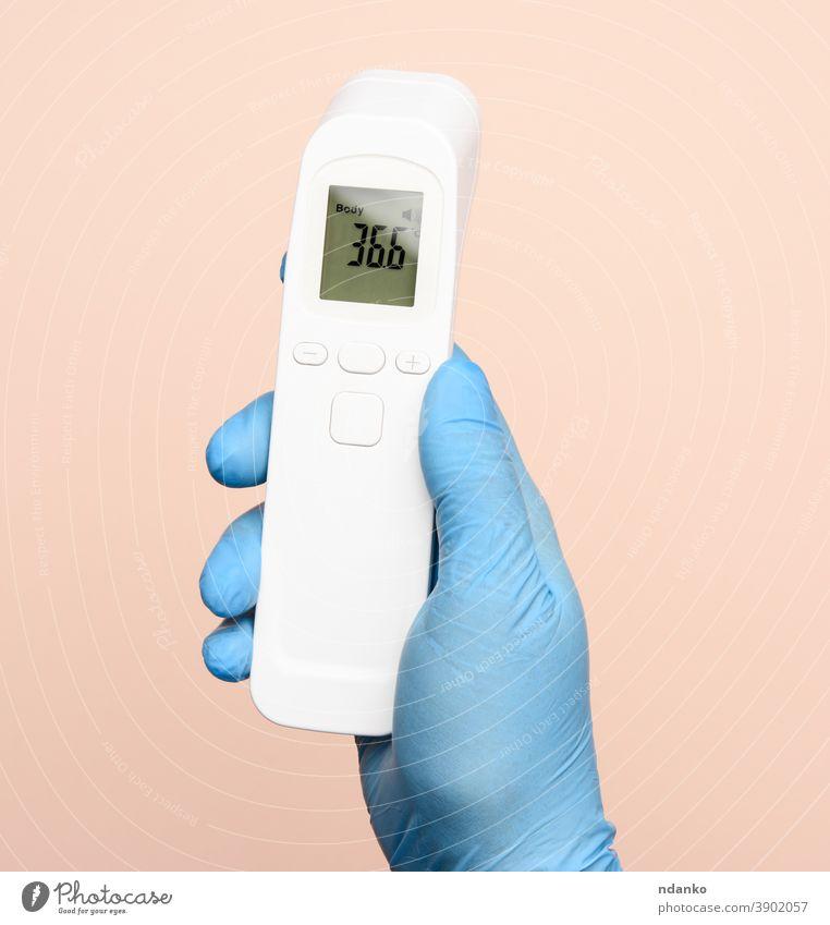 Hand in blauen Latexhandschuhen halten ein elektronisches Thermometer zur Temperaturmessung Technik & Technologie Prüfung Werkzeug Behandlung Virus weiß Körper