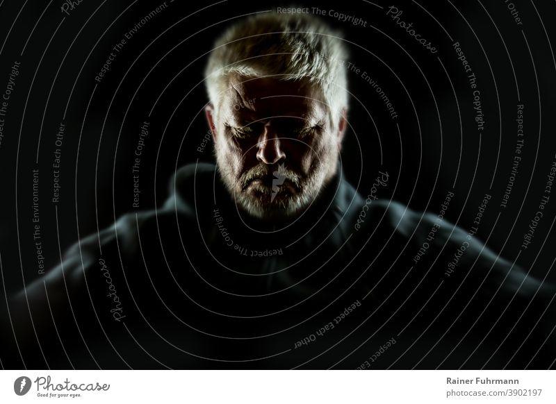 Porträt von einem bärtigen Mann, der einsam in der Dunkelheit sitzt. allein traurig Einsamkeit Depression Traurigkeit unglücklich Person Denken Sorge