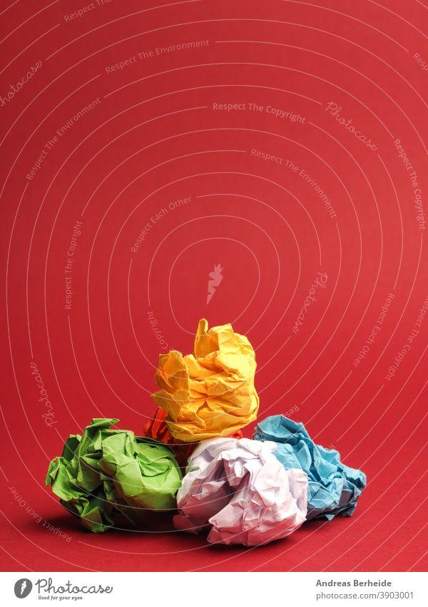 Bunte zerknitterte Papierkugeln auf rotem Studiohintergrund Errungenschaft Ball Tafel Brainstorming hell Knolle Business Konzepte Kreativität Design Fundstück