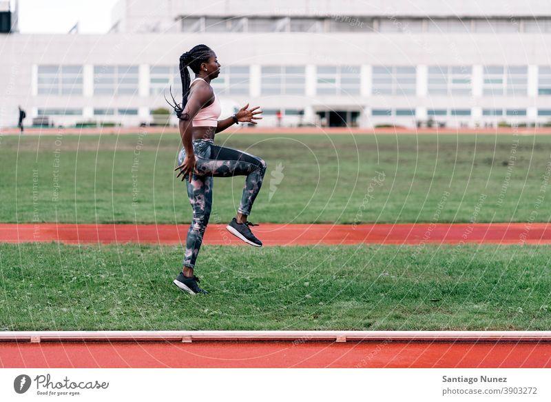 Afrikanisch-amerikanischer Sportler beim Aufwärmen entschlossen muskulös springen Afro-Look Amerikaner Sprinter Beginn Ehrgeiz Motivation Bewegung dynamisch