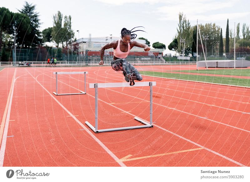 Afrikanisch-amerikanischer Athlet Sprinter springt über eine Hürde entschlossen muskulös springen Afro-Look Amerikaner Beginn Ehrgeiz Motivation Bewegung