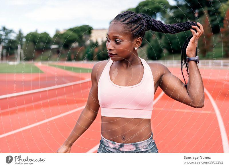 Athlet Sprinter berührt geflochtenes Haar Frau Bahn Leichtathletik Läufer rennen Konkurrenz passen Rennbahn Stadion Training Aktion sportlich Fitness Sport