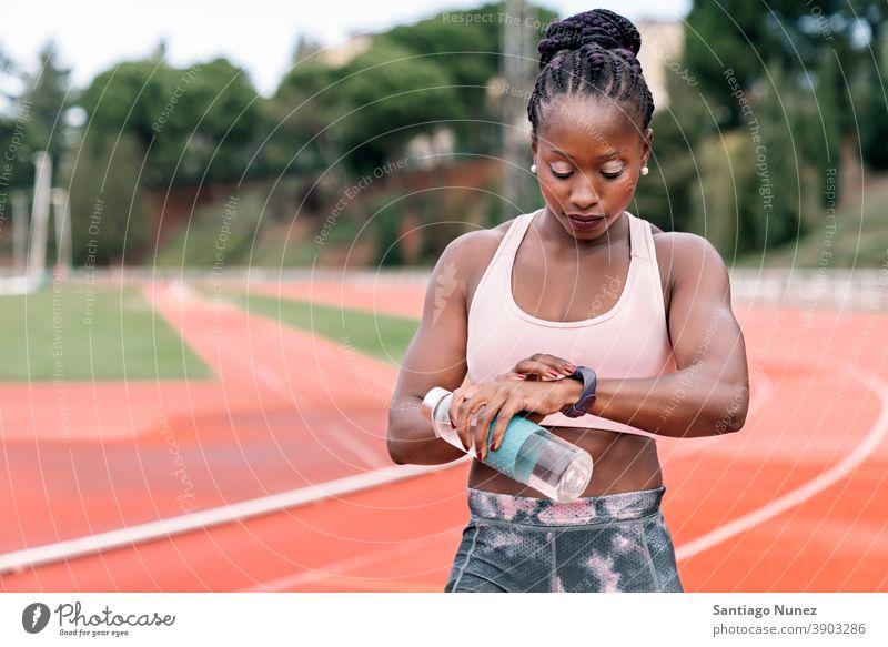 Athlet Sprinter beobachten die Uhr mit einer Flasche Wasser Zeit Start Rennen Training Krawatte Hydratation ethnisch Afro-Look afroamerikanisch Bahn Zug
