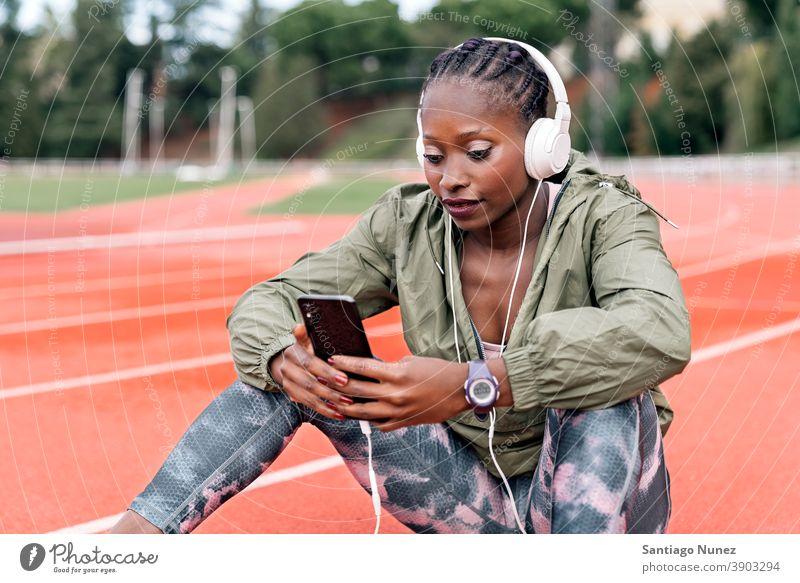 Sportler Sprinter sitzend, Musik hörend Smartphone Afro-Look Konzentration Technik & Technologie Zelle Funktelefon Schutzhelm Mobile Athlet ethnisch