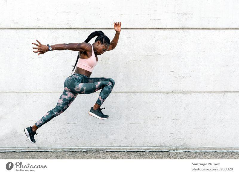 Afrikanisch-amerikanischer Athlet Sprinter springend entschlossen muskulös Afro-Look Amerikaner Beginn Ehrgeiz Motivation Bewegung dynamisch Training Übung