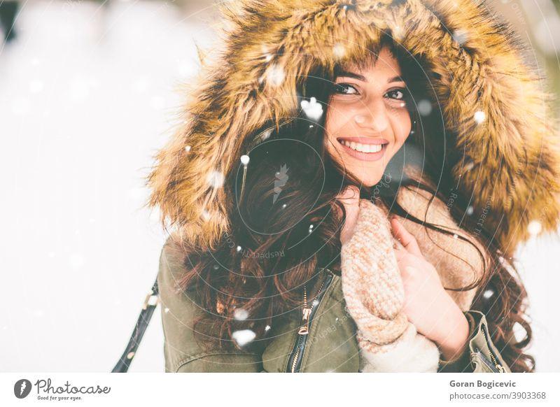 Junge Frau mit Pelzkapuze im Park auf dem Schnee schön Nahaufnahme Kleidung Mantel kalt Mode Fell Mädchen Glück Kapuze Jacke Natur im Freien Porträt hübsch