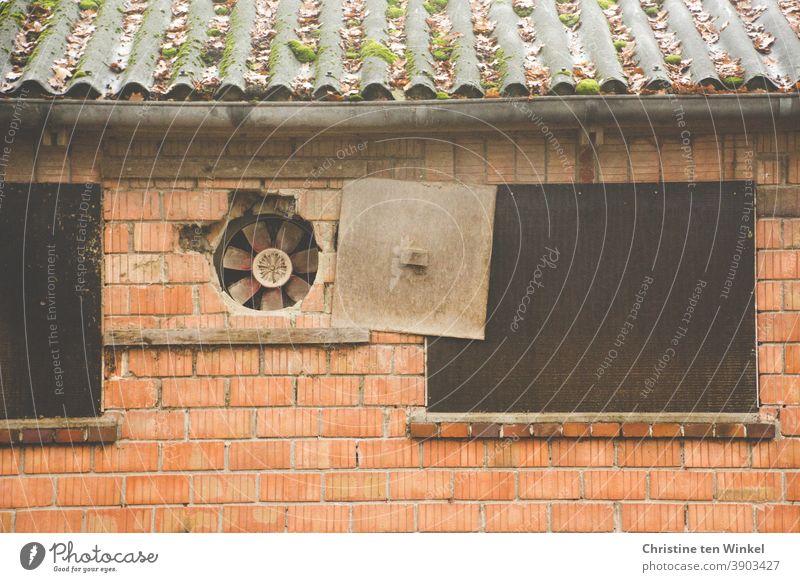 zeitgeschichte | Ventilator in der Außenwand eines alten landwirtschaftlichen Gebäudes mit Blechdach. Die Abdeckplatte ist zur Seite geschoben. Einige Steine beginnen abzubröckeln. Die daneben liegenden Fensteröffnungen sind mit Holzplatten verschlossen.