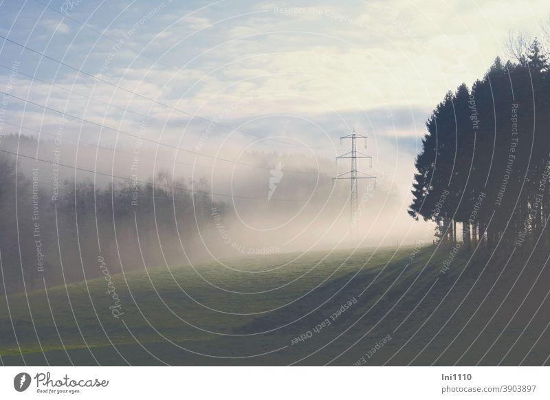 Winterlandschaft mit Nebel und Sonnenschein Naturschauspiel schönes Wetter Hügel Tal Wald Bäume Schatten Sonnenstrahlen Landschaft Strommast Stromleitungen