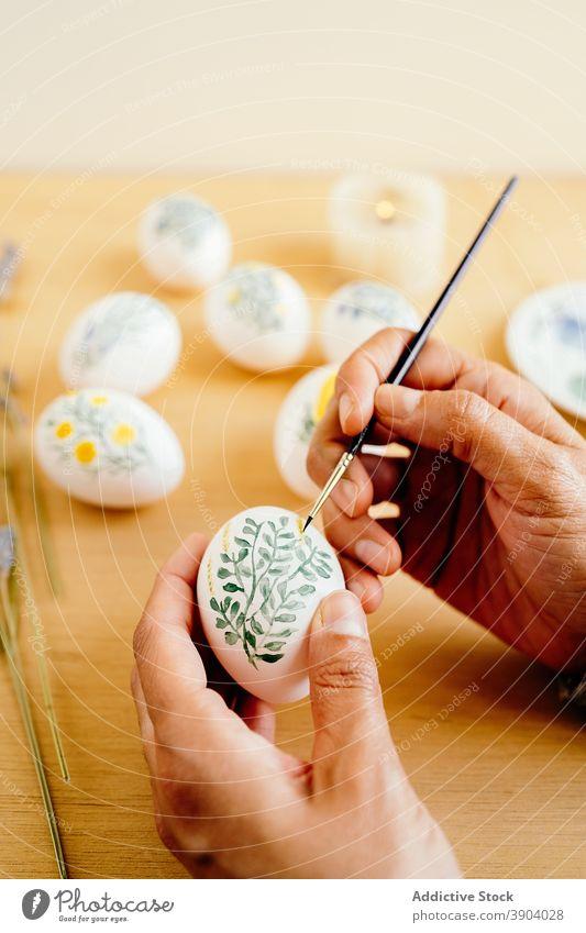 Crop Artist bemalt Eier für Ostern Anstreicher Farbe religiös Feiertag vorbereiten Kunstwerk Blume Frühling Aquarell Lebensmittel Tradition Tisch Religion Dekor