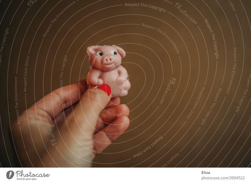 Hand hält kleines Marzipanschweinchen als Glücksbringer für das neue Jahr zu Silvester Schweinchen rosa neues Jahr Glück bringen Glücksschwein Jahreswechsel