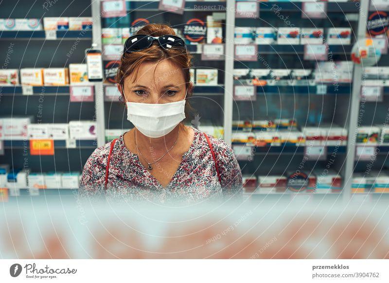 Frau kauft in der Apotheke ein, kauft Medikamente, trägt Gesichtsmaske während des Ausbruchs des pandemischen Coronavirus Chemiker Werkstatt Mundschutz covid-19